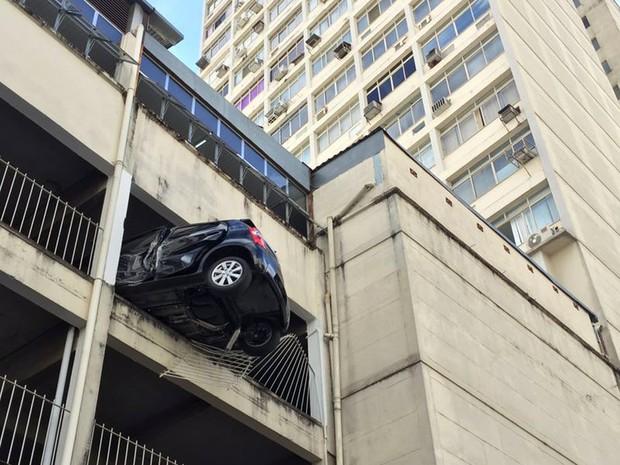 Um carro ficou pendurado na garagem do quarto andar do Edifício Solar do Progesso, na Avenida Barão do Rio Branco, no Centro de Juiz de Fora, na manhã desta quarta-feira (29). (Foto: Sérgio Bara/ publicada em G1 Zona da Mata).